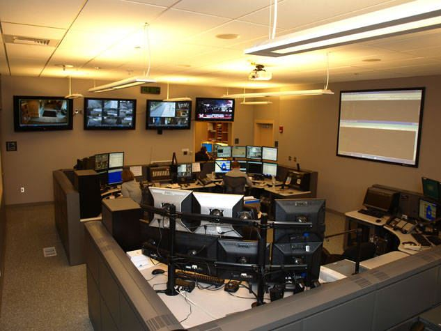 A large communications center with a lot of computers and screens.
