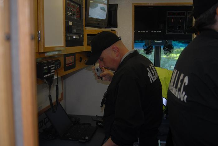 Police officers working in a command truck.